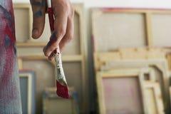 拿着油漆刷的艺术家的手 图库摄影