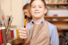 拿着油漆刷的高兴小男孩在艺术课 免版税库存图片