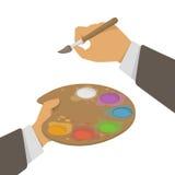 拿着油漆和刷子的手 库存照片