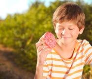 拿着油炸圈饼的孩子男孩户外 库存图片