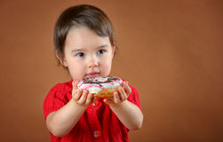 拿着油炸圈饼的小女孩 库存图片