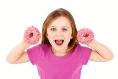 拿着油炸圈饼,被隔绝的背景的笑的女孩 免版税库存图片