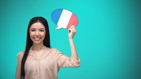 拿着法国旗子讲话泡影的微笑的女孩,学会语言,旅行想法 股票视频