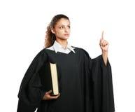 拿着法律书籍的一位年轻女性法官的画象 免版税库存图片