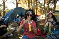 拿着泡影鞭子的微笑的少妇在露营地 免版税库存照片