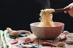 拿着泡面的筷子在杯子有烟上升的和大蒜的妇女手在黑暗的背景,高危险钠的饮食 库存图片