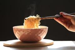拿着泡面的筷子在杯子的妇女手有上升在黑暗的背景,钠饮食高危险的肾衰竭的烟的 免版税库存照片