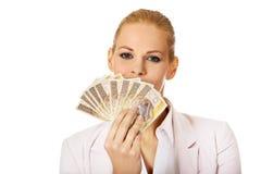 拿着波兰金钱的夹子女商人 免版税库存照片