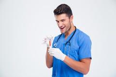 拿着注射器的一位滑稽的男性医生的画象 免版税库存照片