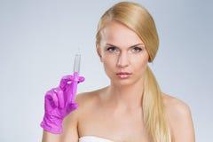 拿着注射器的美丽的白肤金发的妇女手中在手套 库存图片