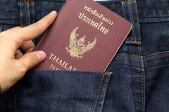 拿着泰国护照插入物的手装在口袋里蓝色牛仔裤气喘 库存照片