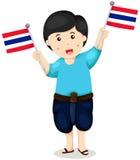 拿着泰国旗子的传统衣裳的逗人喜爱的泰国男孩 免版税库存照片