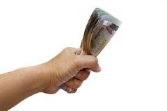 拿着泰国金钱的手。 图库摄影