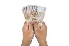 拿着泰国金钱的手被隔绝 免版税库存图片
