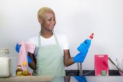 拿着洗涤剂浪花瓶佩带的洗涤的橡胶的年轻有吸引力和愉快的黑美国黑人的妇女清洁家厨房 库存图片