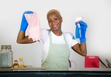 拿着洗涤剂浪花瓶佩带的洗涤的rubb的年轻有吸引力和愉快的黑非裔美国人的妇女清洁家厨房 库存照片