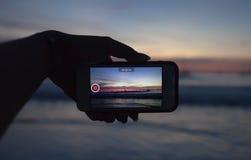 拿着流动巧妙的电话的手和采取日落的录影在夏时的 免版税库存图片