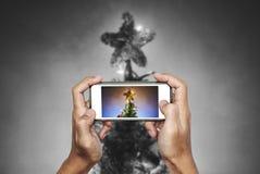 拿着流动巧妙的电话的手,拍圣诞节星照片在圣诞树的与五颜六色的光 免版税库存图片