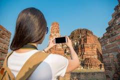 拿着流动智能手机的愉快的女性旅客 库存图片