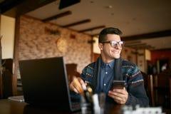 拿着流动现代智能手机的成功的商人 有一个现代电话的愉快的行家享受宜人的新闻 微笑 免版税图库摄影