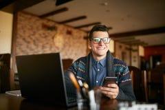 拿着流动现代智能手机的成功的商人 有一个现代电话的愉快的行家享受宜人的新闻 微笑 库存图片