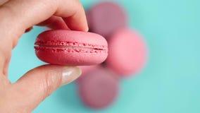 拿着流行粉红法国点心的特写镜头妇女的手 开胃淡色背景 影视素材