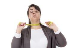 拿着测量的磁带的超重妇女 免版税库存图片