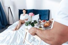 拿着浪漫早餐用新月形面包的男朋友和在他妇女说谎的盘子起来了 免版税图库摄影