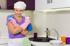 拿着浪花擦净剂和厨房海绵的夫人 免版税库存图片
