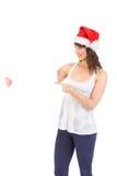 拿着海报的圣诞老人帽子的俏丽的女孩 免版税库存图片