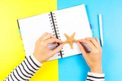 拿着海星、笔和开放笔记本在蓝色和黄色背景的妇女手 库存照片