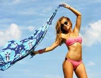 拿着海滩套的年轻性感的白肤金发的女孩对空气使用 库存图片