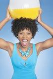 拿着海滩球的可爱的非裔美国人的妇女在高处在色的背景 免版税图库摄影