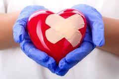 拿着涂灰泥的心脏的医生的手 免版税库存图片