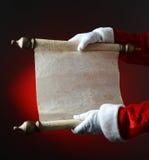 拿着淘气和尼斯纸卷的圣诞老人 免版税图库摄影