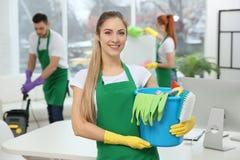 拿着清洁物品的年轻女工在办公室 免版税库存照片