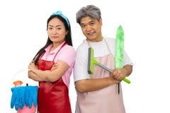 拿着清洁物品的Midle年迈的,年轻亚洲夫妇,当站立在演播室,隔绝在白色背景时,包括剪报 免版税库存照片