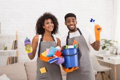 拿着清洗的工具和洗涤剂的非裔美国人的夫妇 免版税库存照片
