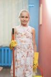 拿着清洁工具的逗人喜爱的少年白肤金发的女孩在厨房里 免版税库存照片