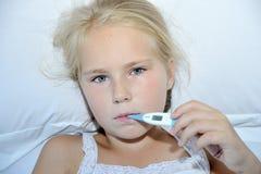 拿着温度计的病的小女孩在床上 免版税库存照片