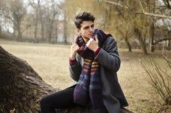 拿着温暖的围巾的年轻时髦的男性在森林里 免版税库存照片