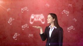 拿着游戏玩家在开放手棕榈的少妇画象` s控制杆,在拉长的演播室背景 到达天空的企业概念金黄回归键所有权 免版税库存照片