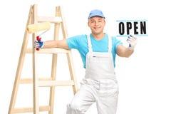 拿着漆滚筒和一个开放标志的房屋油漆工 库存照片