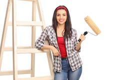 拿着漆滚筒和倾斜在梯子的妇女 库存照片