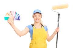 拿着漆滚筒和颜色指南的妇女 免版税库存照片