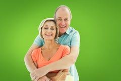 拿着漆滚筒的愉快的更旧的夫妇的综合图象 免版税库存照片
