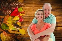 拿着漆滚筒的愉快的更旧的夫妇的综合图象 图库摄影