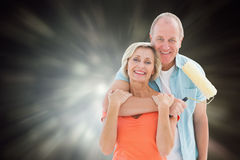 拿着漆滚筒的愉快的更旧的夫妇的综合图象 库存照片