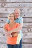 拿着漆滚筒的愉快的更旧的夫妇的综合图象 免版税库存图片
