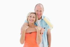 拿着漆滚筒的愉快的更旧的夫妇 库存图片